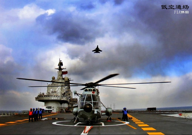 A Chinese Navy Shenyang J-15 carrier based fighter aircraft flies over a Z8 Helicopter