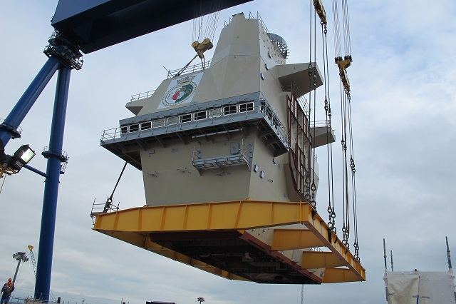 THE AFT island of HMS Queen Elizabeth was lowered into place by Aircraft Carrier Alliance workers in a historic ceremony today (June 28). At the sound of airhorns operated by apprentices Gordon Currie (19) and Chris McArthur (22), teams operating the Goliath crane lowered the iconic section, known as Upper Block 14, the final few feet into place.