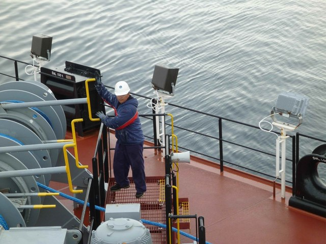 A crew member of Montford Point secures the ship's aft lines as part of the initial mooring operations with Bob Hope.