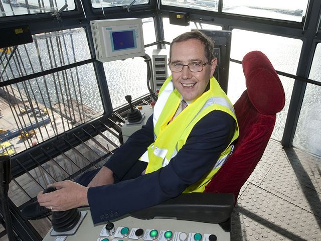Defence Minister Peter Luff at the controls of crane Goliath as it prepares to lift the first section of one of the Royal Navy's new aircraft carriers into place